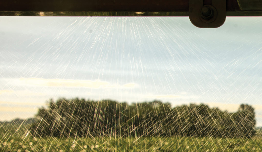 Close-up image of agricultural spray equipment dispensing a herbicide over a growing crop.