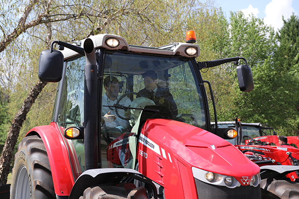 AGCO Marketing Specialist, Taylor Ergle, in Massey Ferguson with FFA's David Townsend.