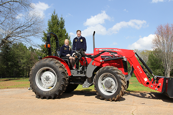 FFA's Valerie Earley and David Townsend on Massey Ferguson tractor at AGCO.