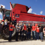 The Doerksen family with their Massey Ferguson MF9560 combine.