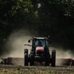 A Massey Ferguson Tractor pulls a vertical tillage machine over farmland in Missouri.