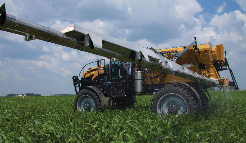 An AGCO RoGator with the AirMax 180 pneumatic spreader applies dry fertilizer to a corn field.