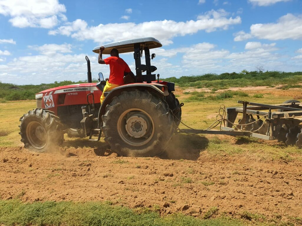 Man drives a red tractor, which pulls a tilling implement behind it